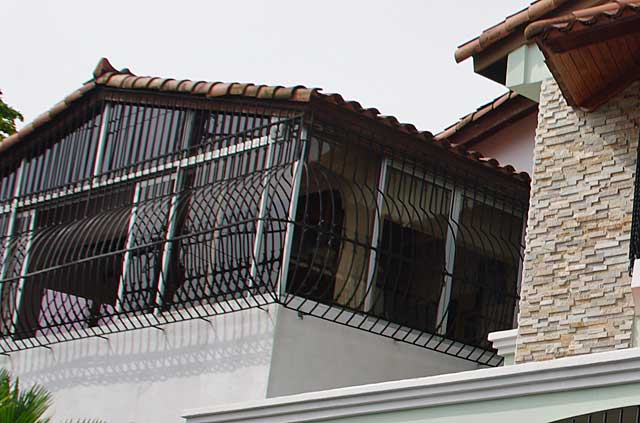 Photograph Of Some Simple But Decorative Metal Security Bars Covering The  Windows Of The Upper Floor Of This House